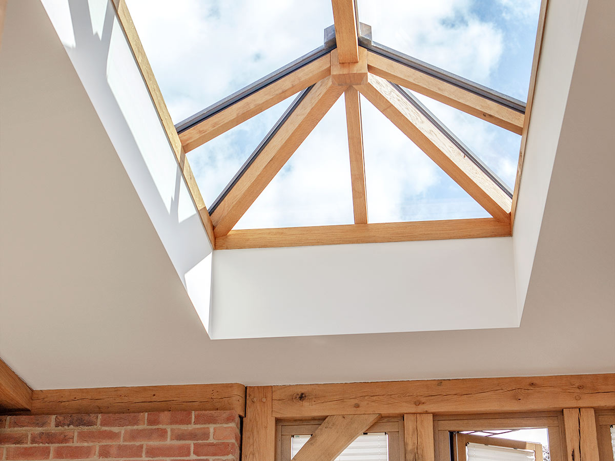 Oak frame orangery extension with flat roof and lantern