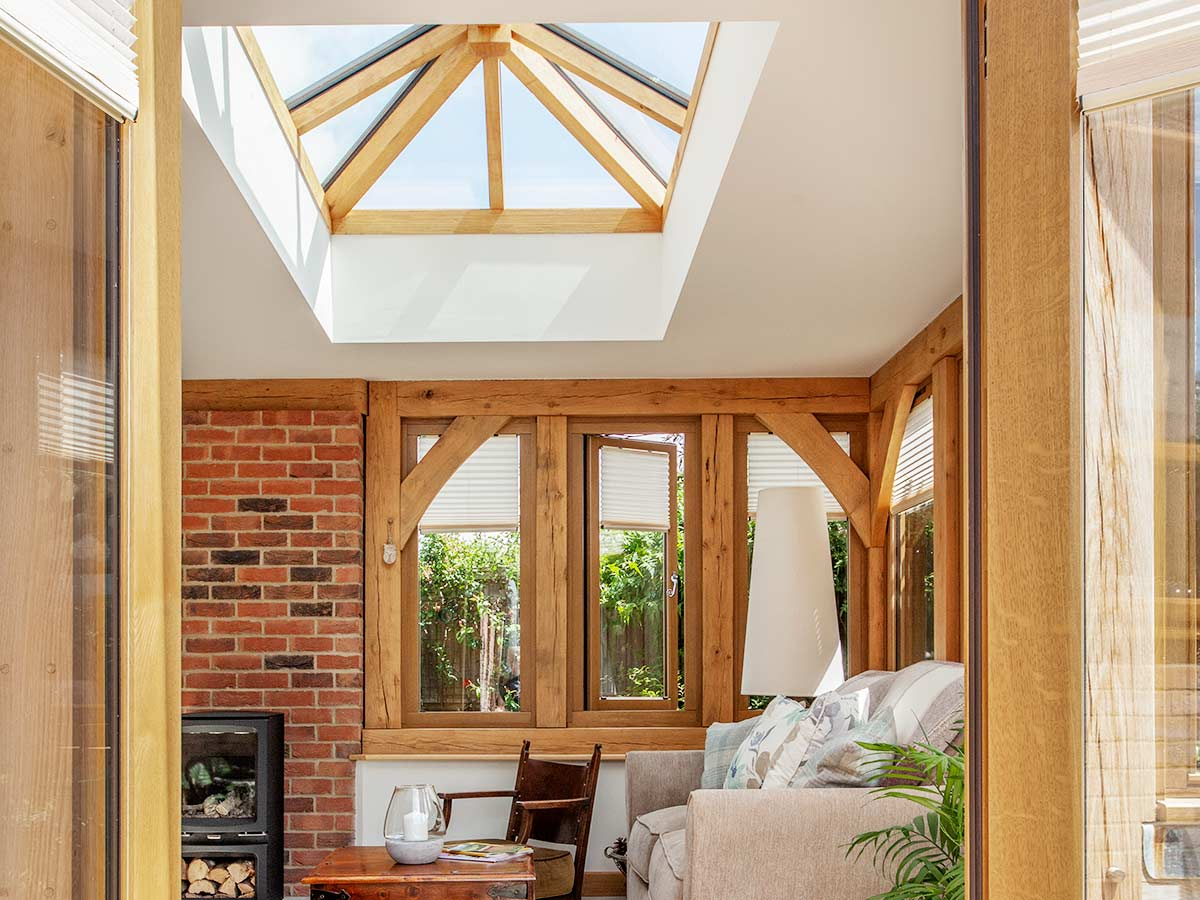 Oak frame orangery extension with lantern and exposed brickwork and woodburner