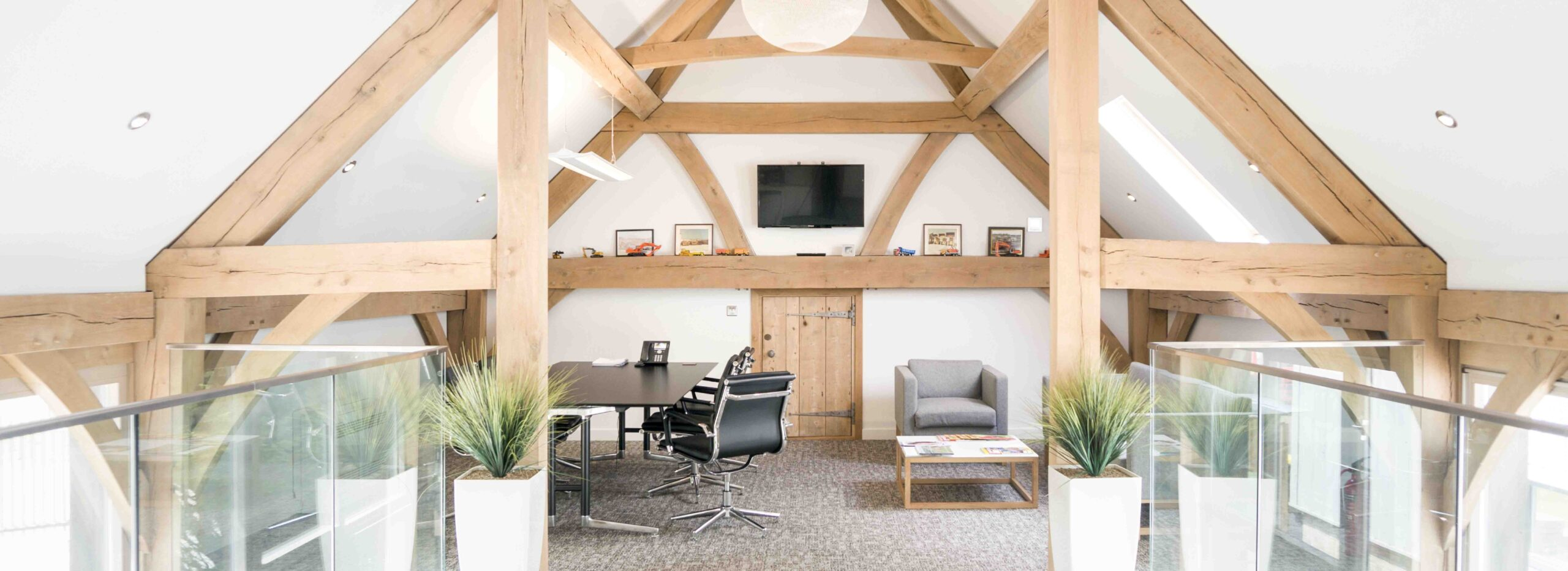 Oak frame offices with desk and chair and vaulted ceiling